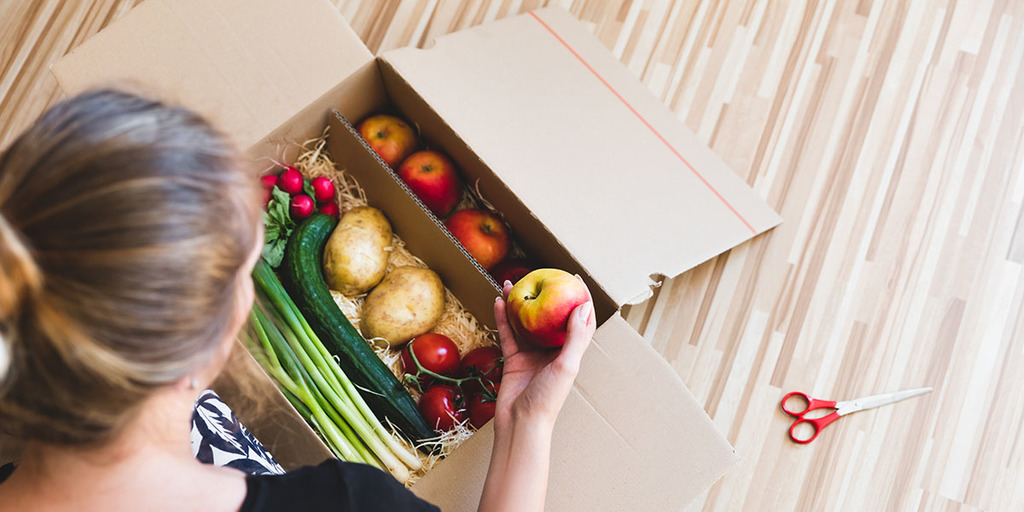 Vegetables grocery box, woman holding a apple