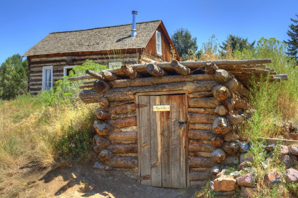 A root cellar built from logs on a homestead