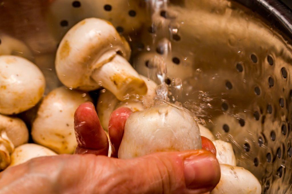 Rinsing button mushrooms in a colander under running water.